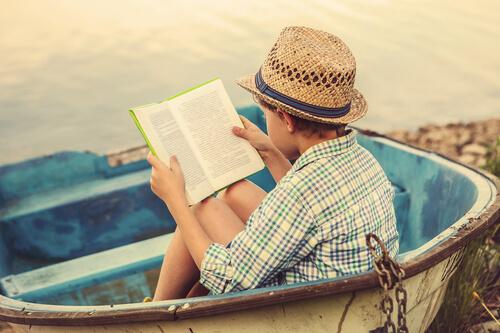 Boy Reading On The Beach