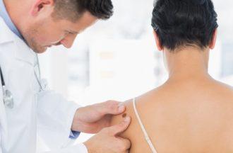 Doctor Examining Melanoma On Woman